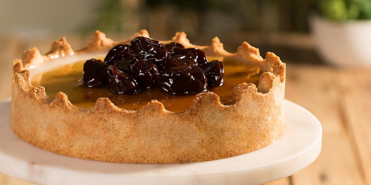 Fotografia em tons de marrom em uma bancada de madeira com um suporte de bolo branco com a torta manjar em cima. Ao lado, um potinho de vidro com ameixas secas pretas.