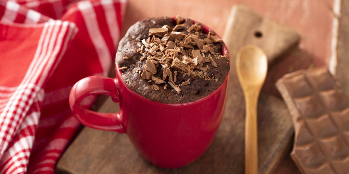 Fotografia em tons de vermelho de uma bancada de madeira, ao centro uma tábua de madeira com uma caneca vermelha e um bolo de chocolate com raspas de chocolate dentro. Ao lado uma pano vermelho com listras brancas e uma colher de madeira.