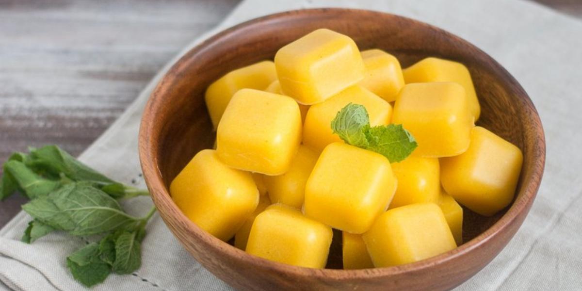 Fotografia em tons de amarelo em uma bancada de madeira, com um pano verde claro com um prato redondo de madeira com as balas cremosas de manga. Ao lado, limões espremidos e folhas de hortelã.