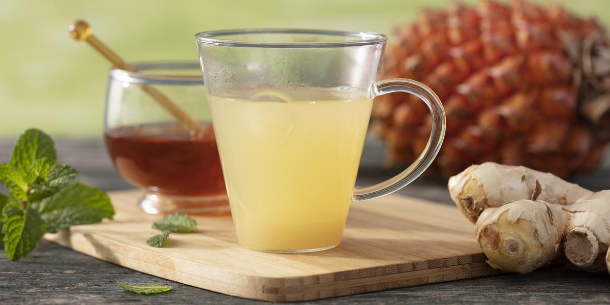 Fotografia em tons de amarelo em uma bancada de madeira cinza, uma tábua de madeira com uma xícara de vidro com o chá de casca de abacaxi dentro dela. Ao lado, um potinho com mel, um pedaço de gengibre e folhas de hortelã. Ao fundo, um abacaxi.
