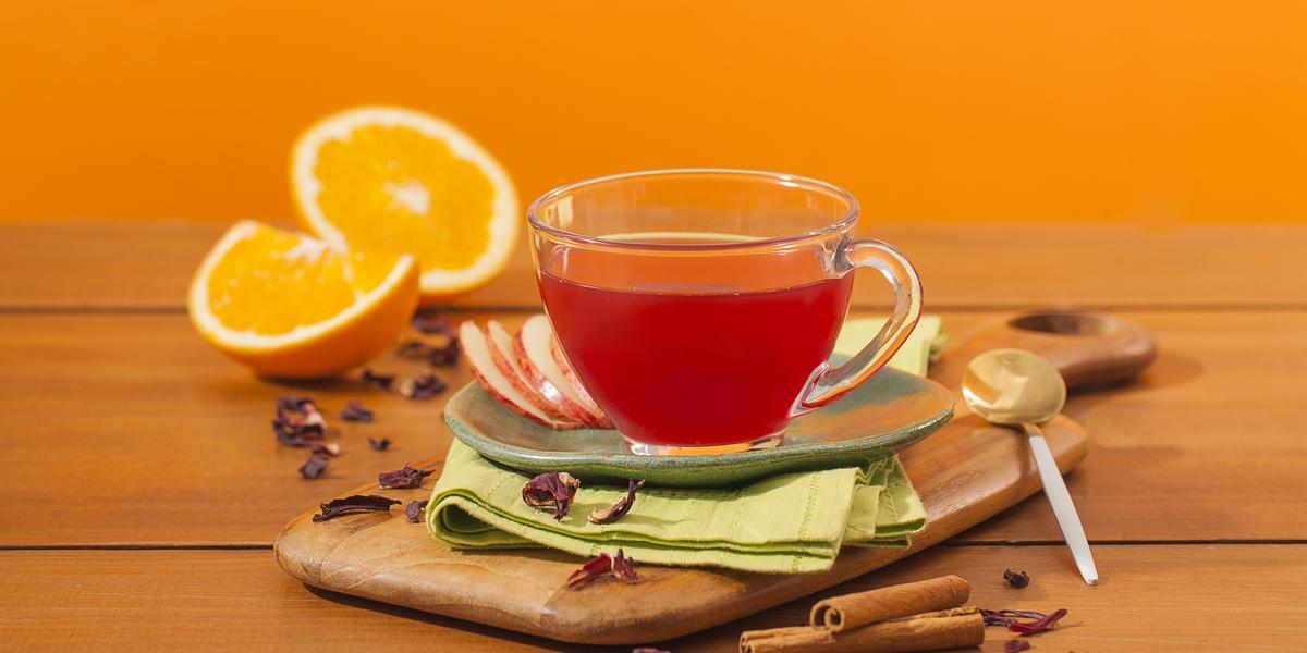 Fotografia em tons de laranja em uma bancada de madeira e um fundo laranja. Ao centro, uma tábua de madeira, um paninho verde e uma xícara de vidro com o chá de hibisco dentro dele. Ao fundo, laranja e canela em pau espalhados pela bancada.