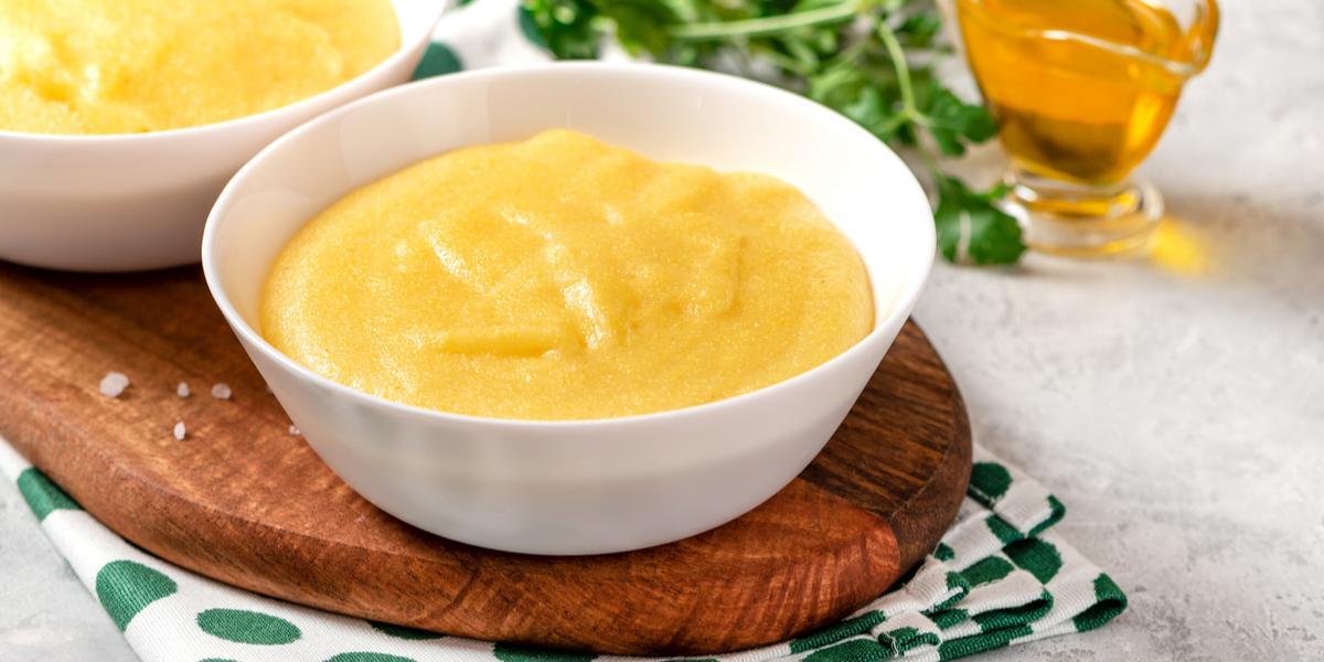 Na fotografia contém um pano branco com bolinhas verdes, por cima uma tábua de madeira de ponta redonda. Acima da tábua dois potes brancos com polenta dentro e ao lado um potinho com azeite.