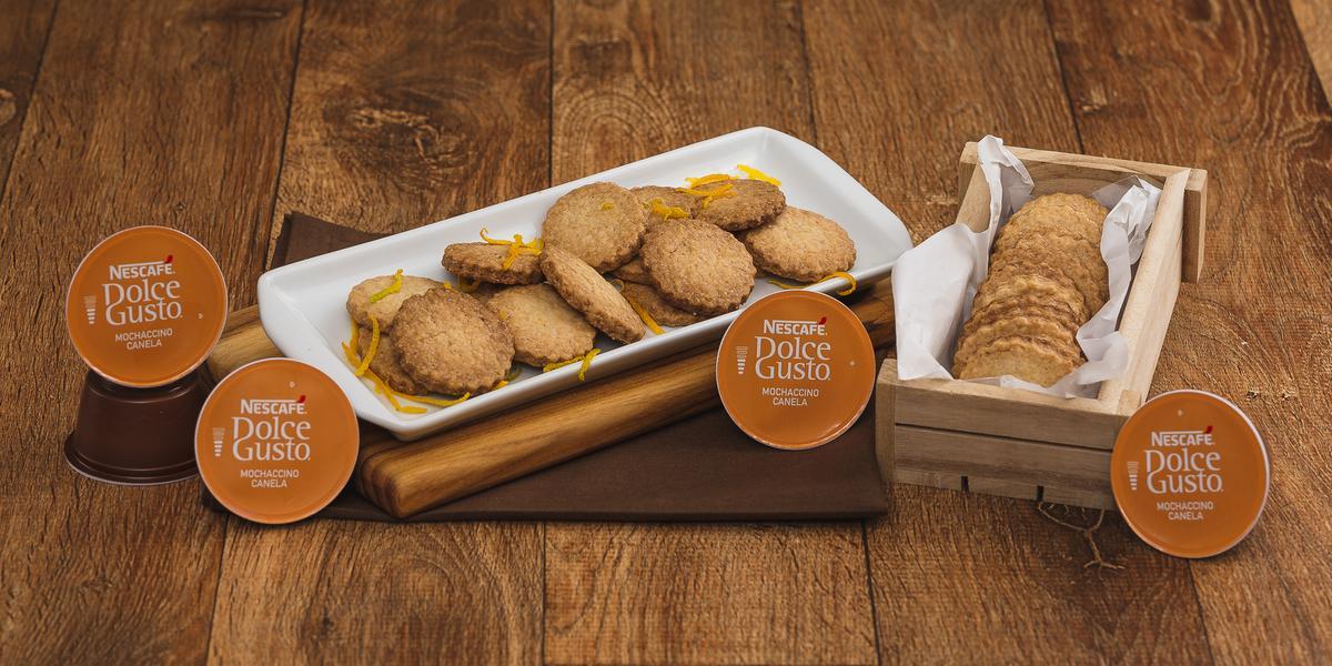 Fotografia em tons de marrom em uma bancada de madeira escura, um pano marrom com uma tábua de madeira em cima dele e um recipiente branco com vários biscoitos amanteigados com raspas de laranja em cima deles. Ao lado, uma caixinha com mais biscoitos.