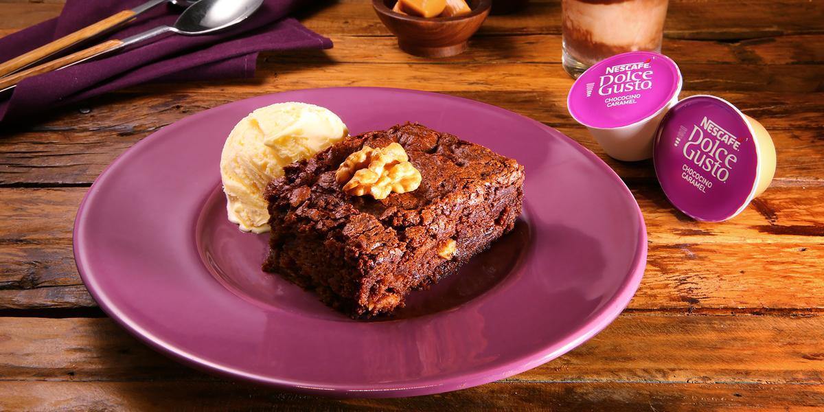 Fotografia em tons de roxo em uma bancada de madeira escura, um prato redondo roxo com o brownie com uma bola de sorvete de creme ao lado. Ao fundo, um pano roxo com uma colher e um garfo e ao lado uma xícara com o chococino caramel Dolce Gusto.