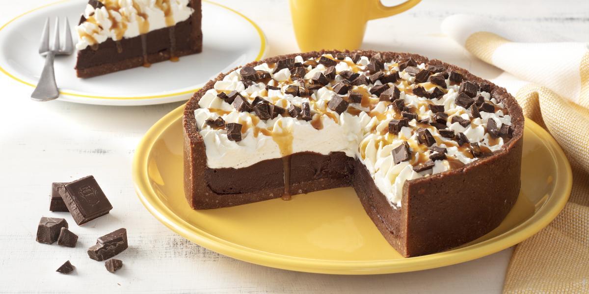 Fotografia em tons de amarelo em uma bancada branca com um prato grande amarelo e a torta de chocolate com caramelo em cima cortada ao meio. Ao lado, um prato branco com uma fatia da torta de chocolate, uma xícara amarela e pedaços de chocolates.