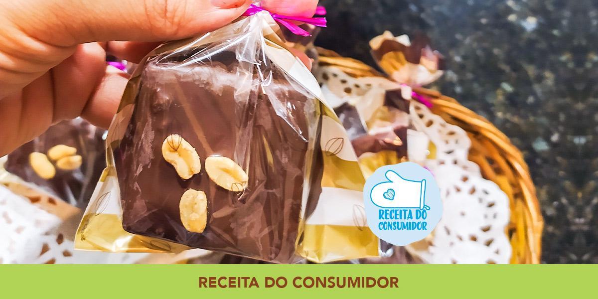 Fotografia em tons de amarelo em uma bancada de pedra preta com uma cesta de vime, uma mão segurando uma embalagem de plástico com a palha italiana dentro dela.