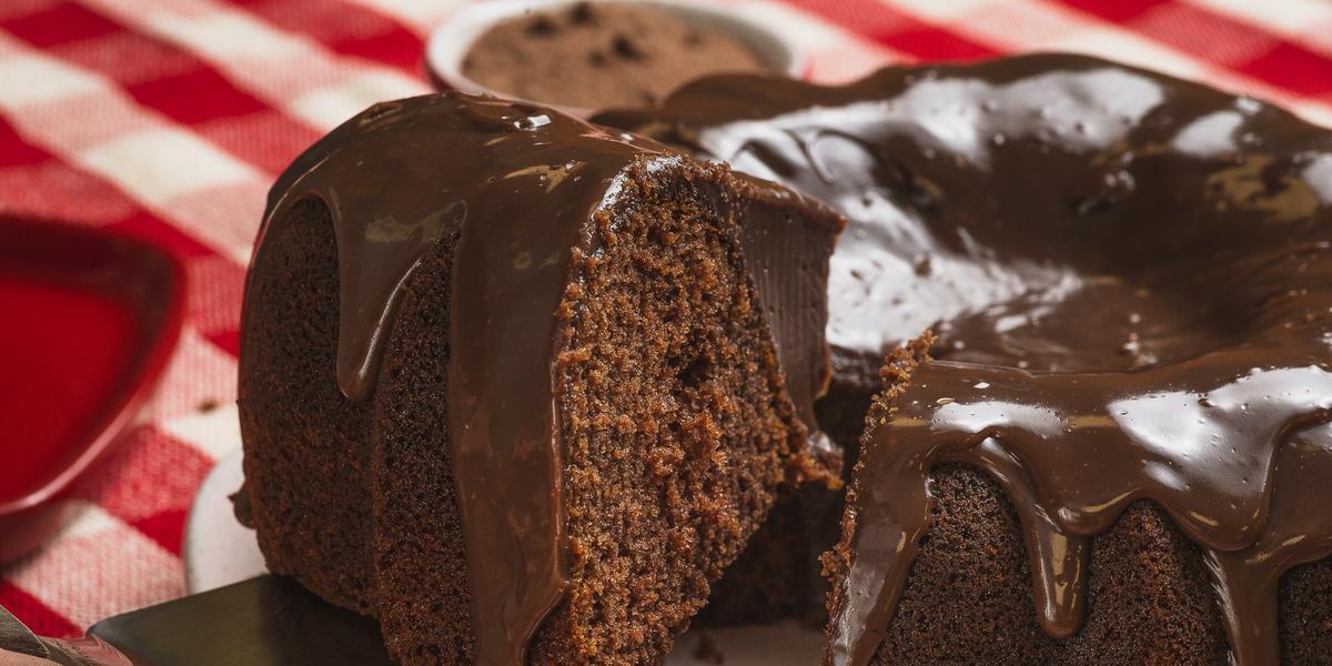Foto bem aproximada de um bolo de chocolate com uma fatia sendo retirada. O bolo está num prato branco e coberto com Brigadeiro e o prato está sobre uma toalha xadrez vermelho e branco.