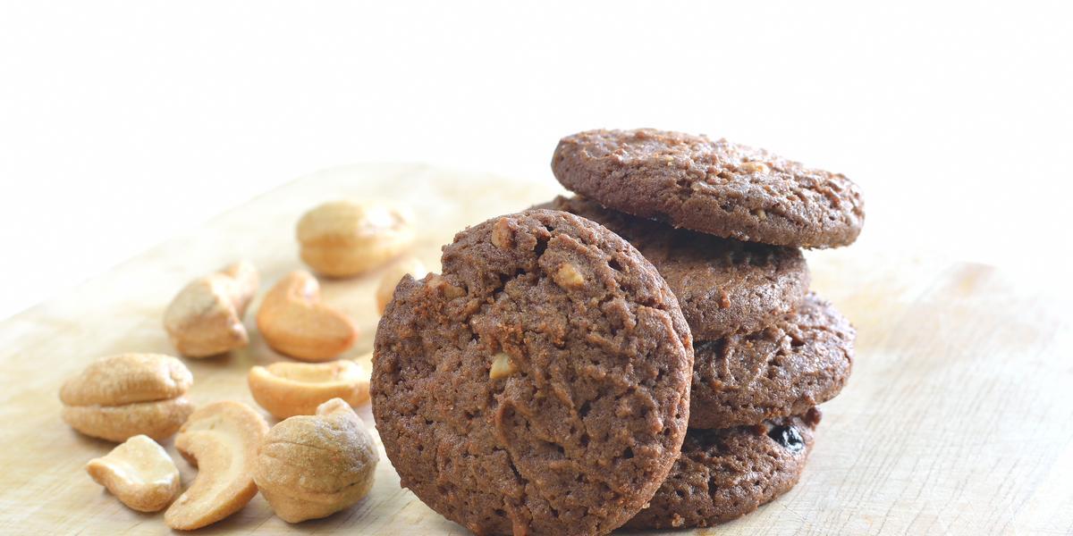 fotografia em tons de branco, marrom e bege de uma bancada bege vista de frente, ao centro biscoitos de chocolate e ao lado castanhas de caju