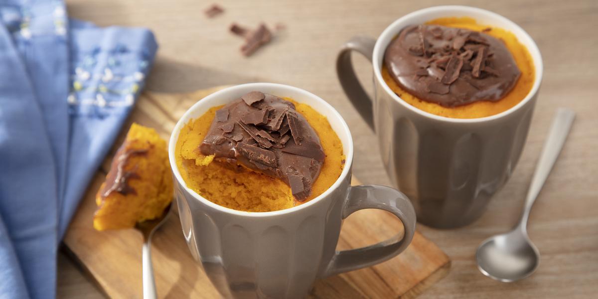 Fotografia em tons de laranja em uma bancada de madeira clara, uma tábua de madeira, um paninho azul, duas canecas marrons com o bolo de cenoura dentro de cada uma e por cima o brigadeiro de Nescau.