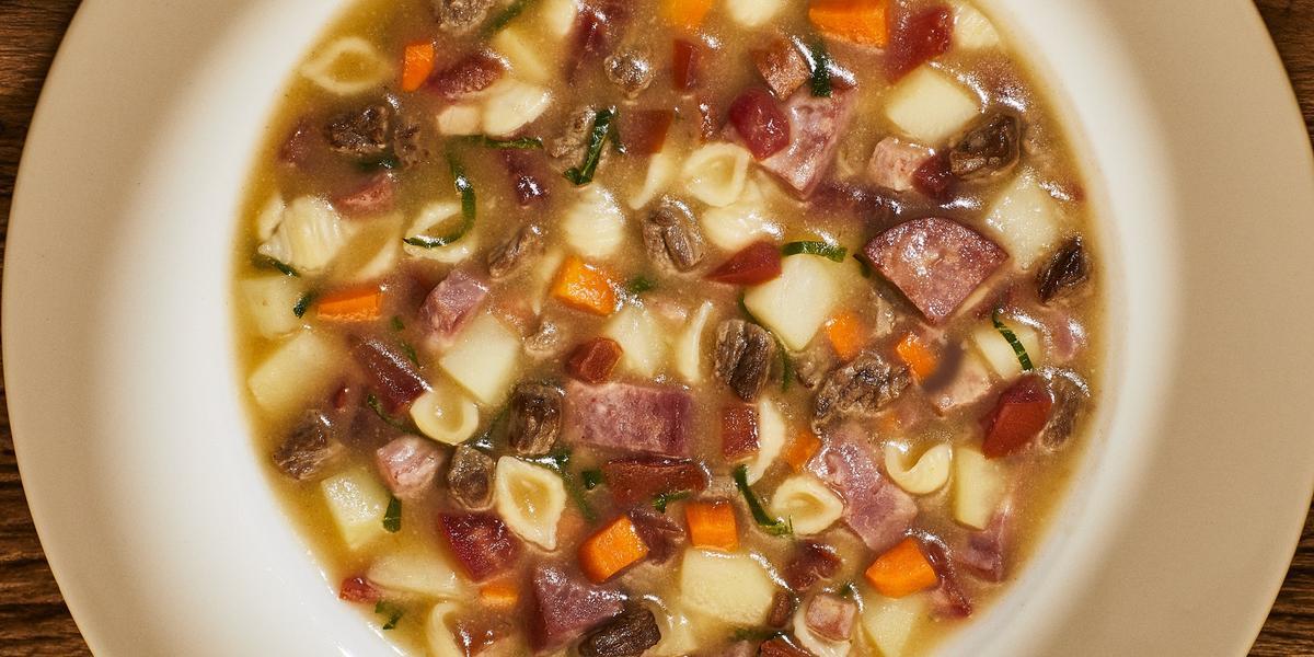 Foto bem aproximada de um prato branco fundo no qual está a receita pronta de sopão de carne com legumes e linguiça