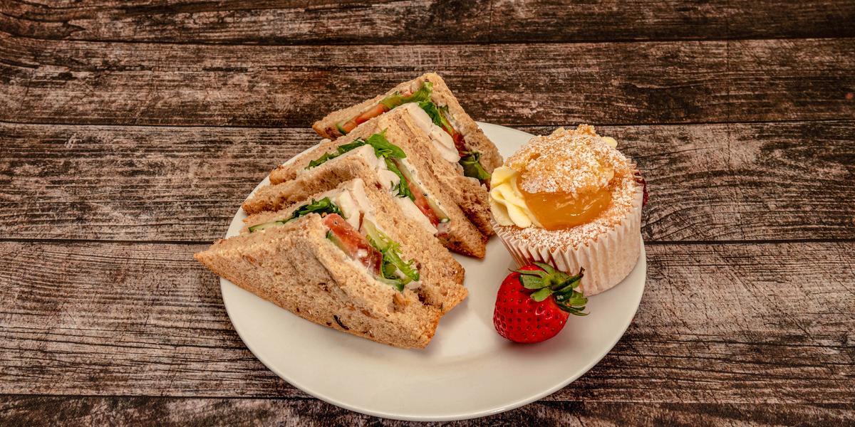 fotografia em tons de marrom de uma bancada vista de cima. Contém um prato redondo branco com fatias de pães de forma com recheio de frango, folhas de alface e tomates.