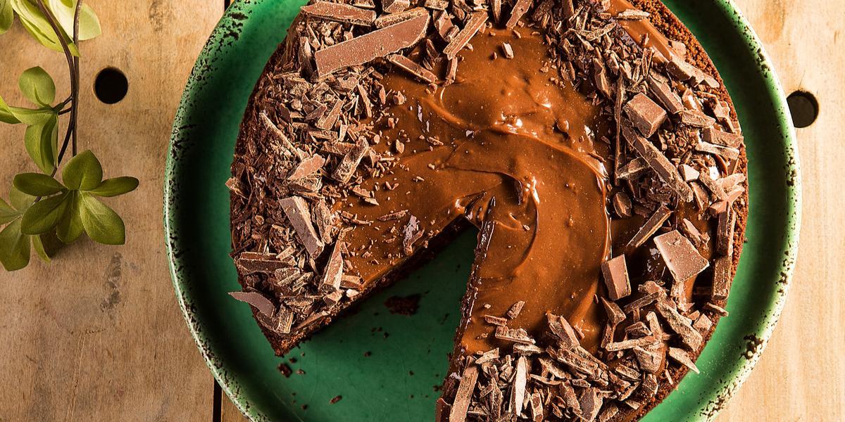 Fotografia em tons de verde em uma bancada de madeira clara com um suporte verde com o bolo de chocolate em cima. Ao lado, um prato com uma fatia do bolo e uma espátula para bolo.