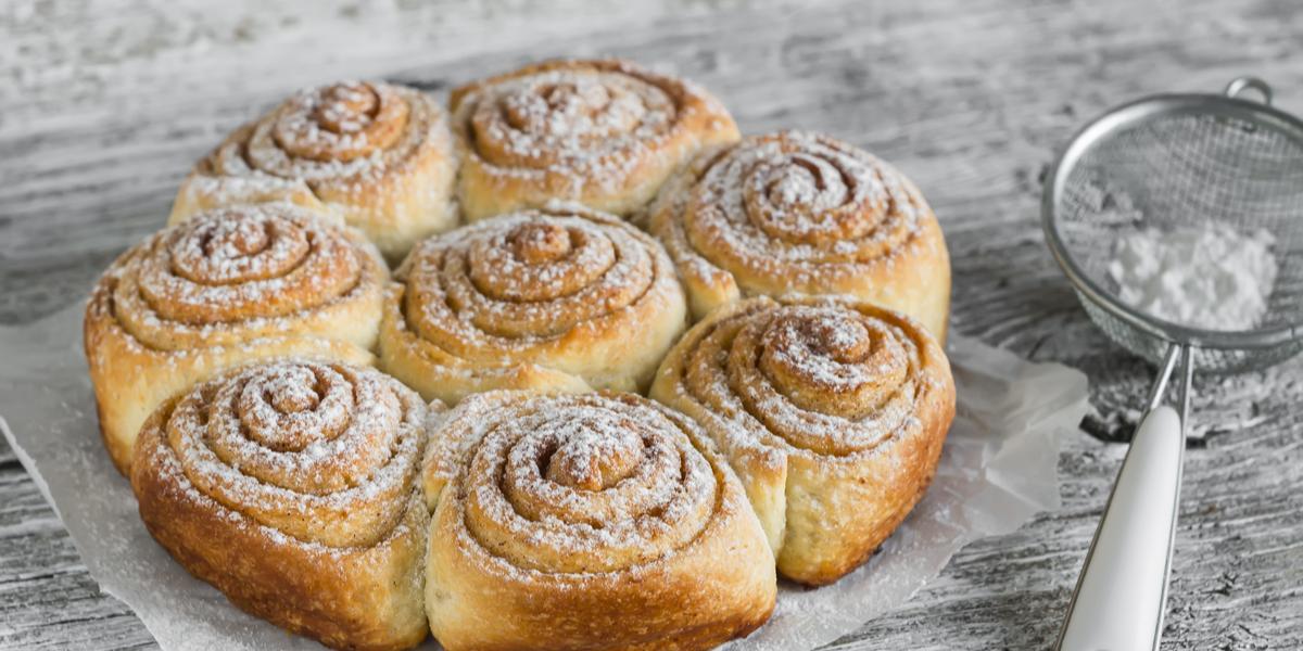 Em uma bancada cinza contém diversos pães redondos com açúcar por cima, ao lado uma peneira com açúcar.