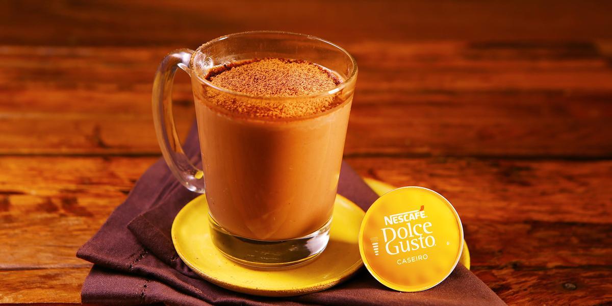 Fotografia em tons de amarelo em uma bancada de madeira escura, um prato amarelo redondo, um pano marrom e uma xícara de vidro com o chocafé com chocolate dentro dela.