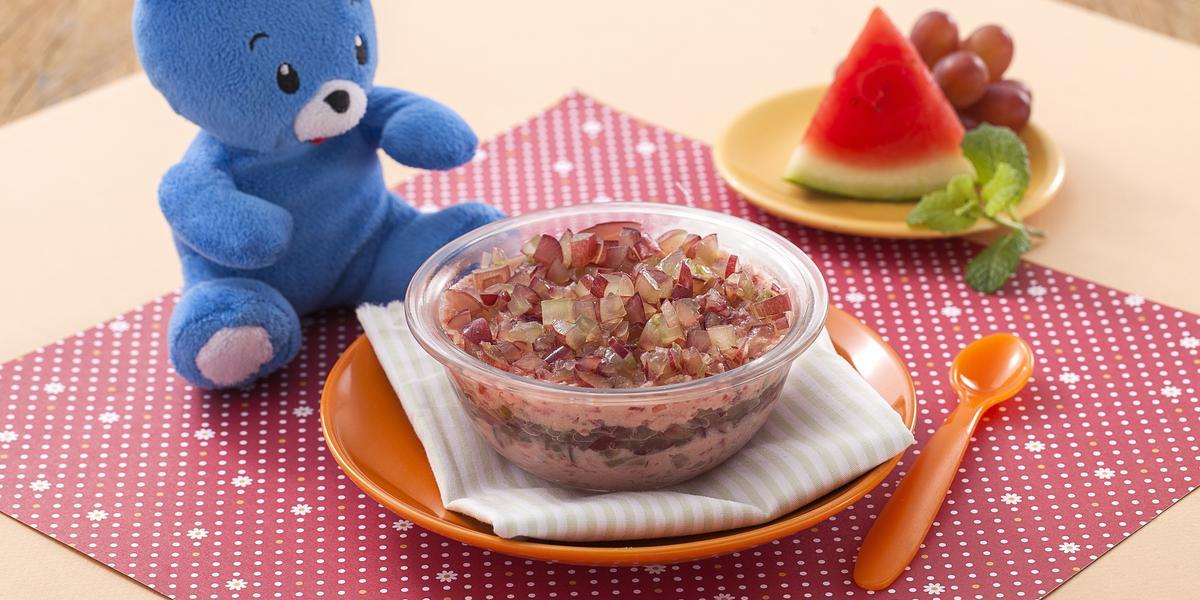 Fotografia em tons de rosa em uma bancada de madeira com um potinho transparente com creminho de melancia e uva. Ao lado, uma colher pequena laranja, um pratinho amarelo com uma fatia de melancia e um cacho de uva e um ursinho de pelúcia azul.