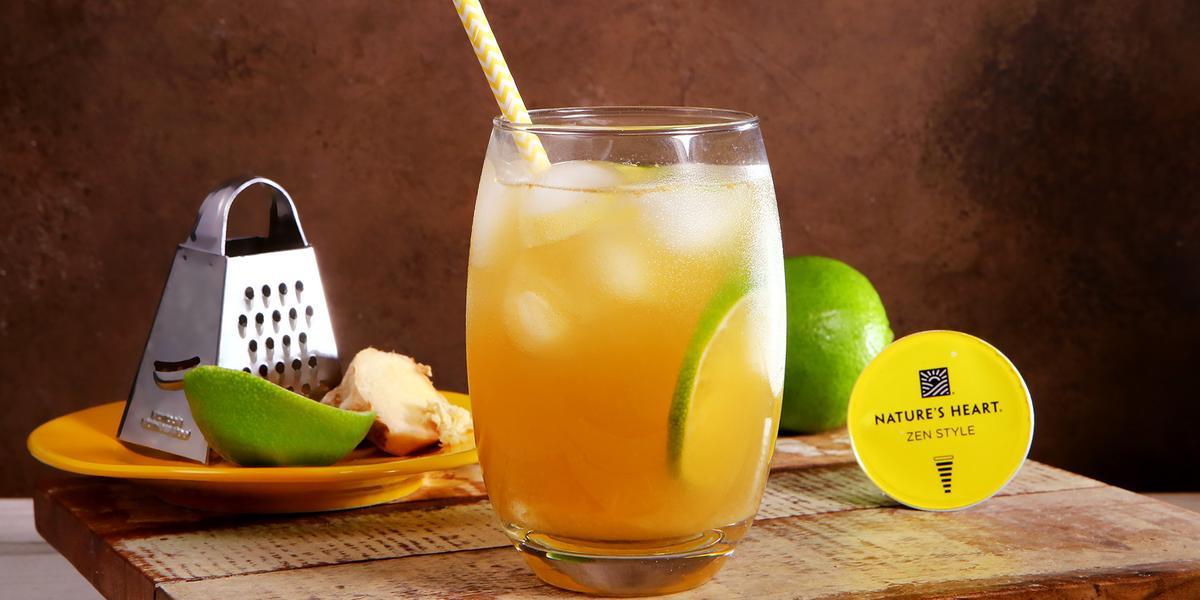 Fotografia em tons de amarelo e verde em uma bancada com uma tábua de madeira clara, um copo de vidro com o chá de gengibre com limão dentro dele. Ao fundo, um ralado, uma fatia de gengibre e um pedaço de limão e cápsula do chá Zen Style Nature´s Heart.