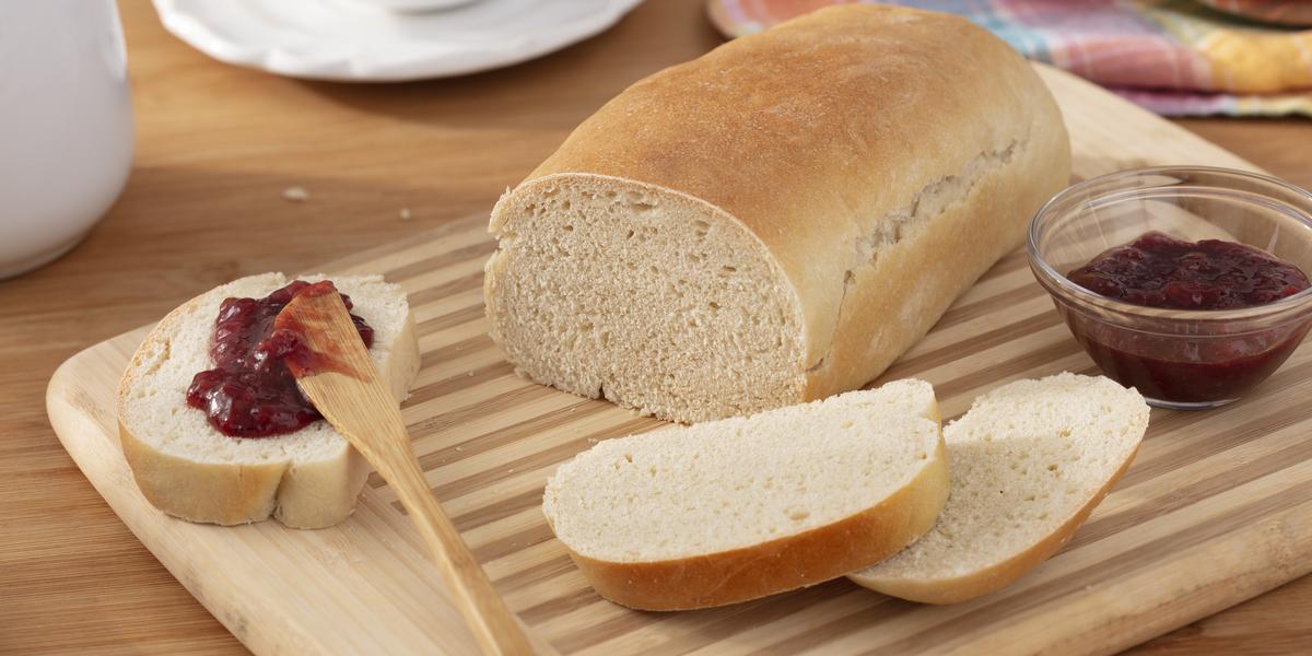 Fotografia em tons de bege em uma bancada de madeira clara, um pano azul colorido em tons pasteis, uma tábua de madeira clara com um pão de forma com fatias e um potinho de geleia ao lado. Ao fundo, uma xícara branca de café e um bule branco.