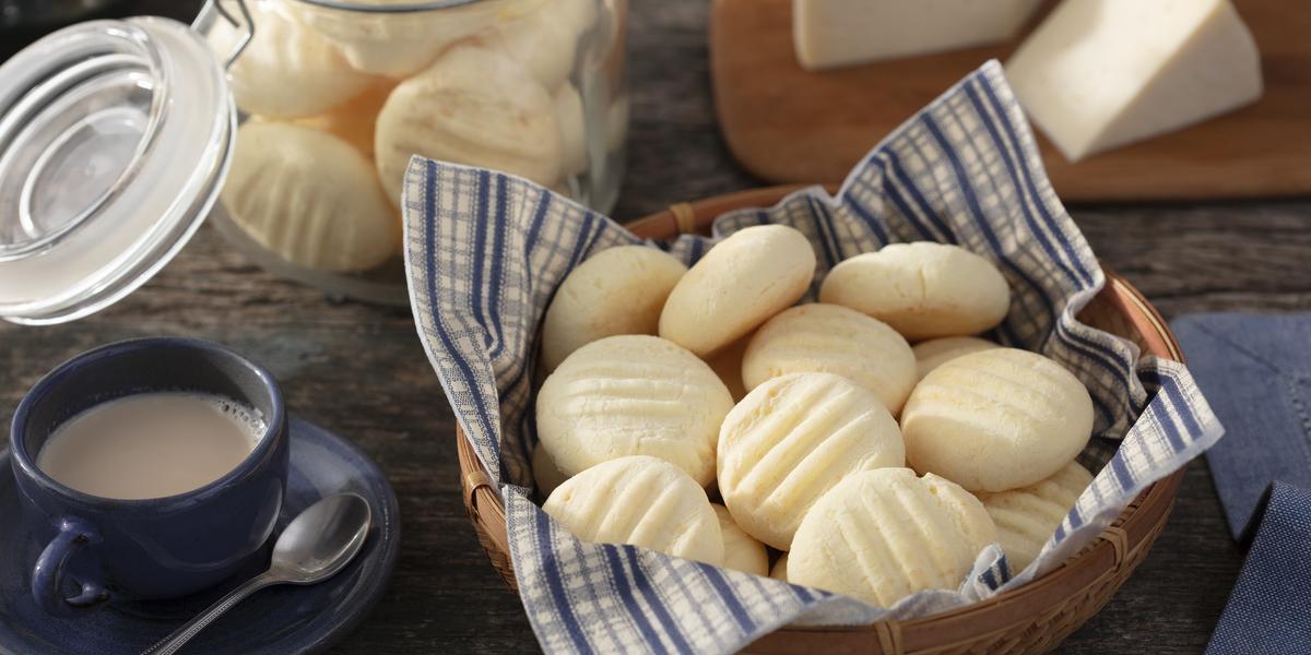 Fotografia em tons de azul em uma bancada de madeira escura, uma cesta de vime com um guardanapo de papel azul listrado com biscoitos de queijo dentro dele. Ao lado, uma xícara de café. Ao fundo, uma tábua de madeira com um pedaço de queijo.