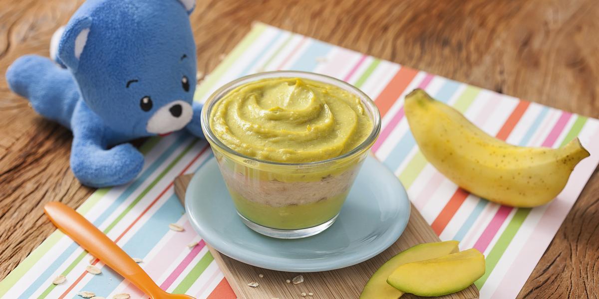 Fotografia em tons de verde em uma bancada de madeira, com um paninho listrado colorido e uma tacinha transparente com abacate e banana apoiado em um pratinho azul. Ao lado, um ursinho de pelúcia azul, uma colher laranja e uma banana.