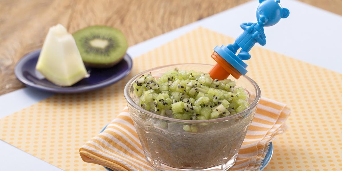Fotografia de uma bancada de madeira com paninho laranja com bolinhas, um potinho transparente com uma papinha e cubinhos de kiwi e uma colher de ursinho azul. Ao fundo um pratinho com um pedaço de melão e um pedaço de kiwi.