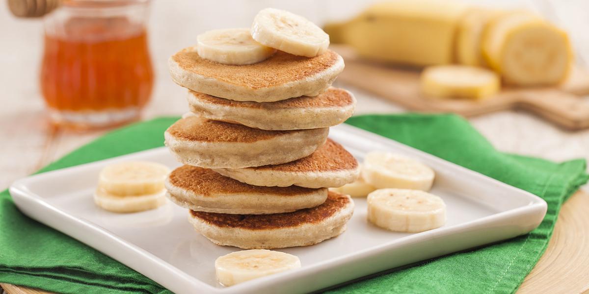 Fotografia em tons de verde em uma bancada de madeira clara, uma tábua de madeira redonda com um pano verde em cima, um prato quadrado branco e seis panquequinhas empilhadas com rodelas de banana em torno delas. Ao fundo, um potinho de mel e uma banana.