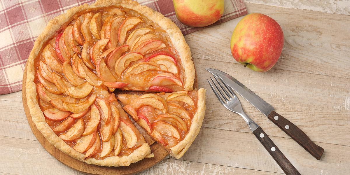 fotografia em tons de bege e vermelho de uma bancada bege vista de cima, um prato redondo marrom com uma torta de maçã que contém fatias de maçã por cima. De um lado um pano xadrez em tons de vermelho e branco com duas maçãs, e do outro garfo e faca.