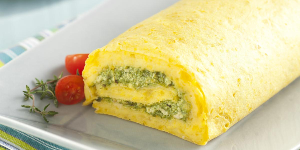 Fotografia em tons amarelados com um paninho listrado em azul, cinza e amarelo e um prato retangular com o rocambole de espinafre, mandioquinha e tofu em cima. Ao fundo, um prato com um pedaço do rocambole e um garfo azul ao lado.