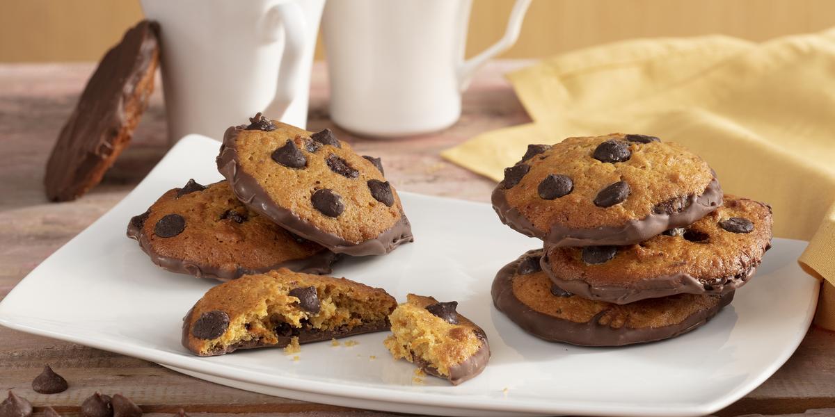 Fotografia em tons de amarelo em uma bancada de madeira com um pano amarelo, um recipiente quadrado branco com alguns cookies de cenoura recheado com chocolate. Ao fundo, duas xícaras brancas com café.