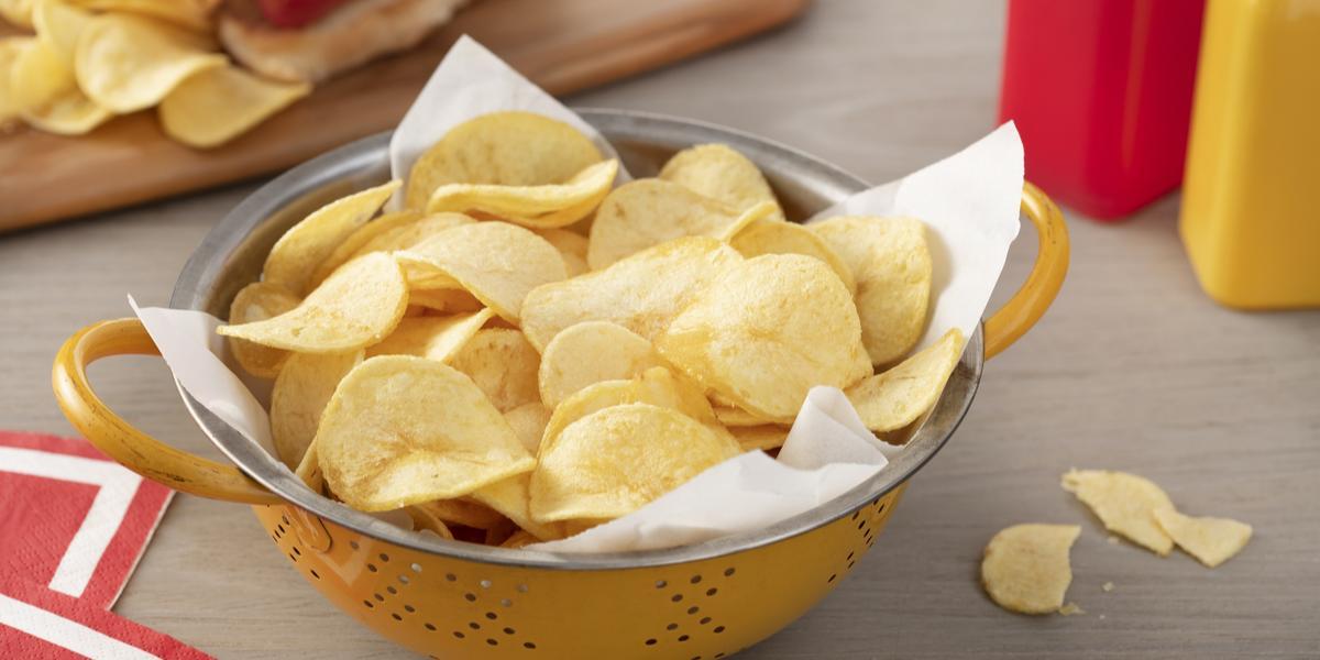 Fotografia em tons de vermelho em uma bancada de madeira clara, um pano vermelho com listra branca, uma tábua de madeira com um cachorro-quente e batatas chips ao lado. Ao centro, um recipiente redondo amarelo com muitas batatas chips.