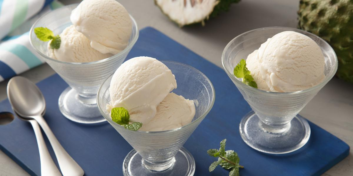 Fotografia em tons de branco e azul de uma bancada, ao centro uma tábua azul, com três taças com duas bolas de sorvete de graviola cada. Ao fundo, uma graviola cortada ao meio.