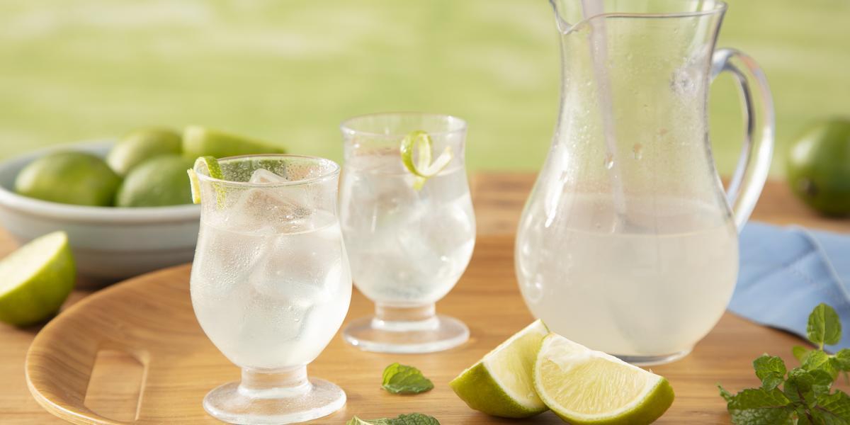 Fotografia em tons de verde em uma bancada de madeira clara com um gramado ao fundo, uma badeja de madeira com uma jarra de vidro com a limonada e dois copos ao lado com a limonada servida, limão e folhas de hortelã espalhadas na bandeja.