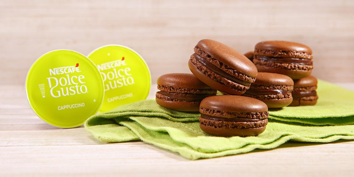 Fotografia em tons de verde em uma bancada de madeira clara, um paninho verde com vários macarons de chocolate e café em cima dele. Ao lado, cápsulas de Cappuccino Dolce Gusto.