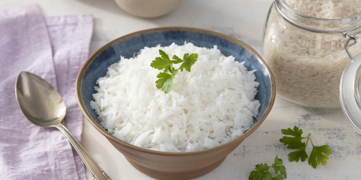 Fotografia em tons de lilás em uma bancada de madeira clara, um pano lilás e um pote marrom redondo fundo com o arroz basmati dentro dele. Ao lado, um pote hermético com arroz cru e uma colher de servir.