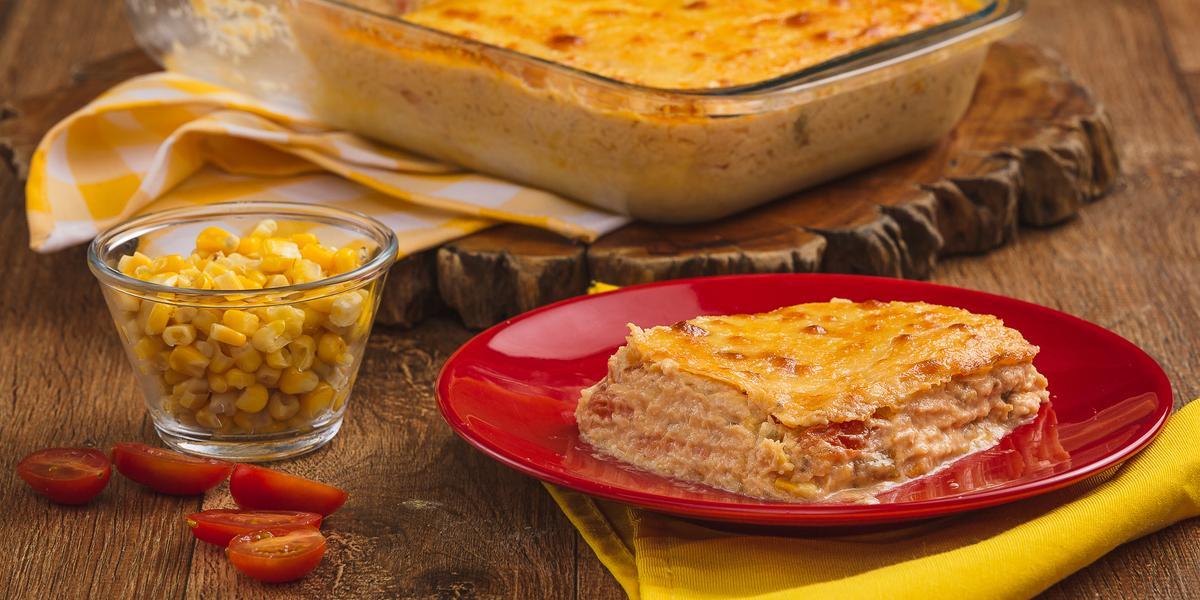 Imagem aproximada da receita de fricassé, com um pedaço em um prato vermelho sobre um pano amarelo e o restante em uma travessa transparente ao fundo. Há também um pote com milho e alguns tomates pequenos cortados ao meio do lado esquerdo.