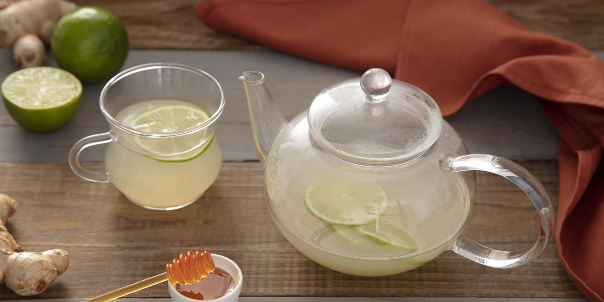Fotografia em tons de verde em uma bancada de madeira escura, um bule de vidro com o chá de gengibre e limão dentro. Ao lado, uma xícara com o chá e uma fatia de limão e um potinho com mel. Gengibre e limões espalhados pela mesa.