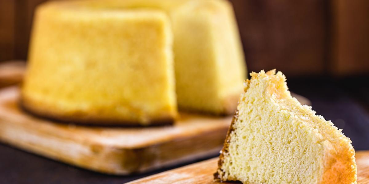 Fotografia em tons de marrom e amarelo de uma bancada azul escura vista de frente, duas tábuas de madeira uma com uma fatia de bolo e a outra com o bolo redondo sem uma fatia