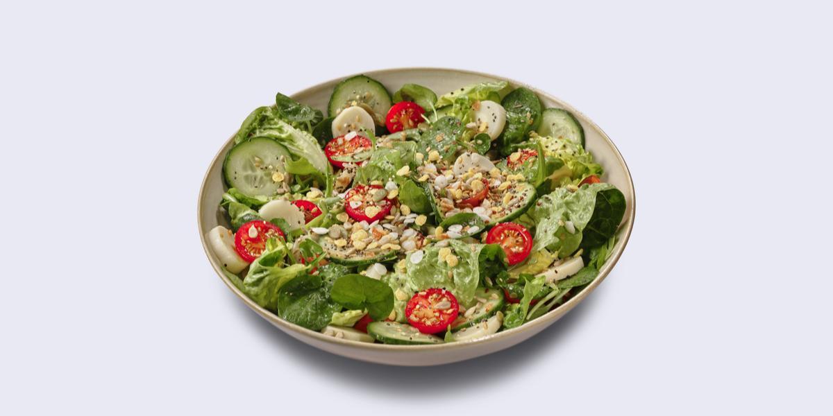 Fotografia em tons de verde em um fundo branco com um prato fundo redondo com a salada verde.