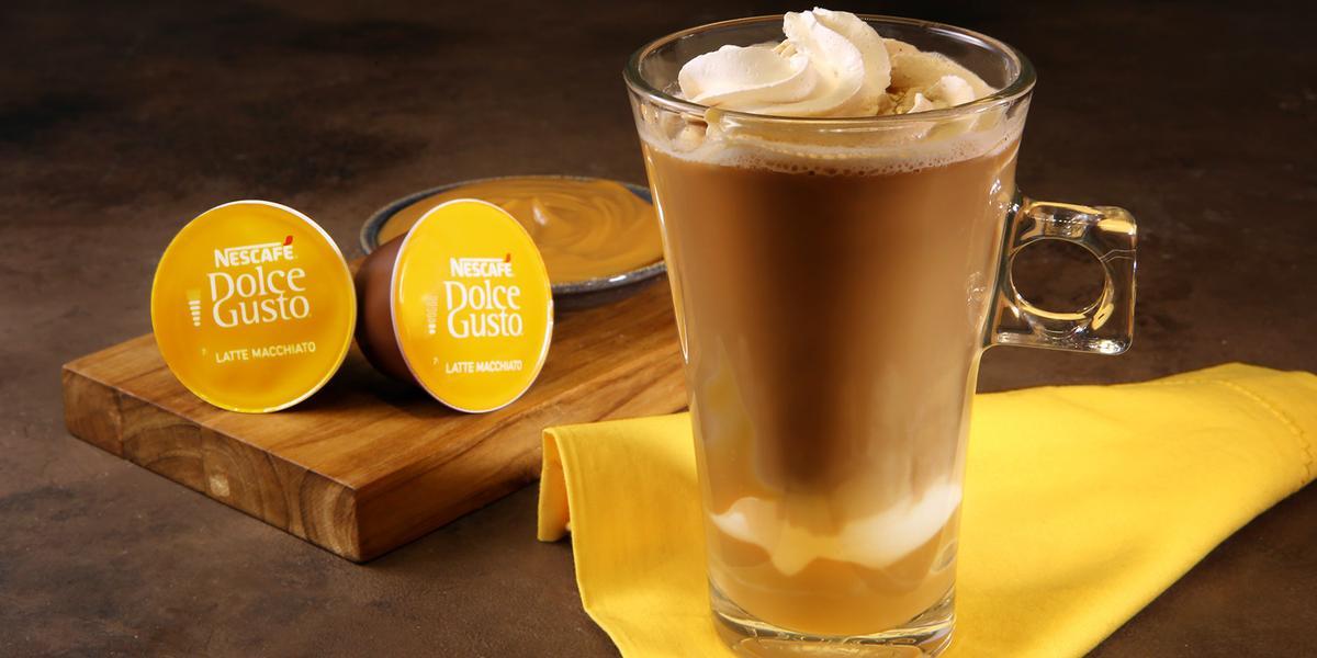 Fotografia em tons de amarelo em uma bancada de madeira escura, um paninho amarelo, uma xícara de vidro alta com o Latte Macchiato Dolce Gusto dentro, com doce de leite e decorado com chantilly. Ao fundo, cápsulas do café e um potinho com doce de leite.