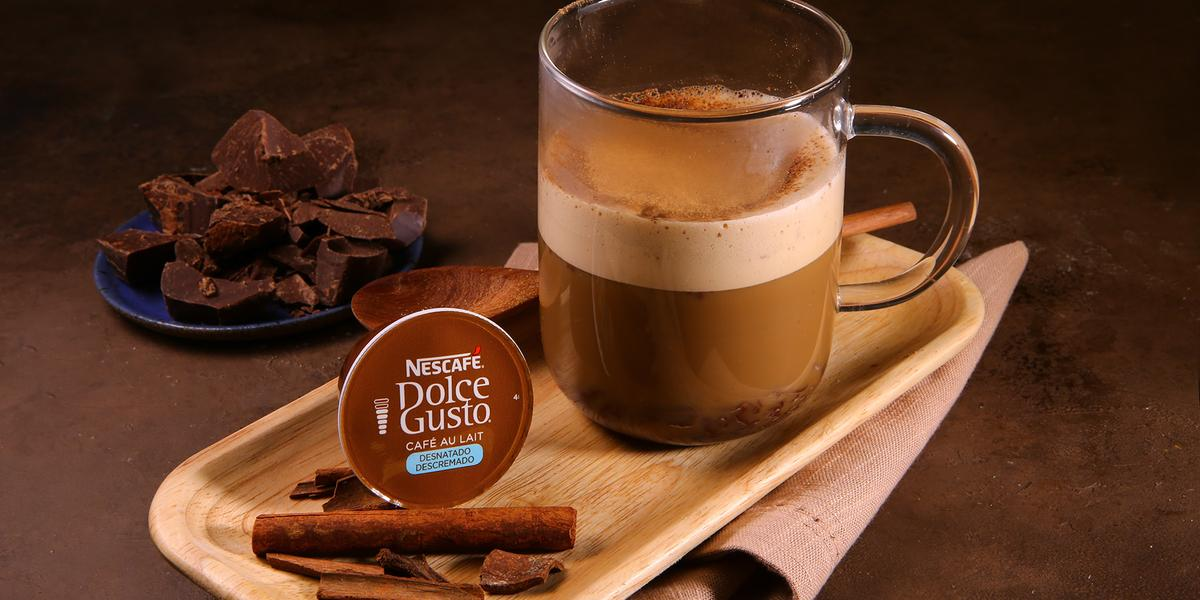 Fotografia em tons de marrom em uma bancada de madeira marrom escura, um recipiente oval de madeira clara, um pano bege, uma xícara de vidro com a bebida de café ao leite desnatado com chocolate e canela dentro dela. Ao fundo, pedaços de chocolate.
