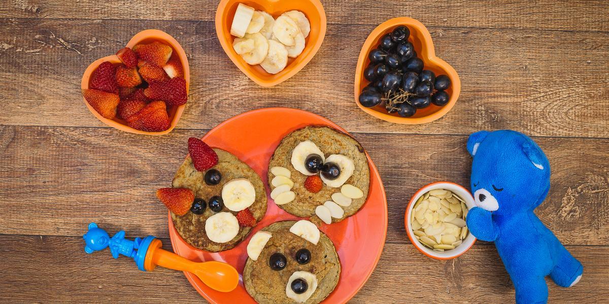 Fotografia em tons de laranja em uma bancada de madeira escura, um prato laranja com três panquequinhas com rostinho de bichinhos em cada uma delas, potinhos com frutas e um ursinho azul de pelúcia.