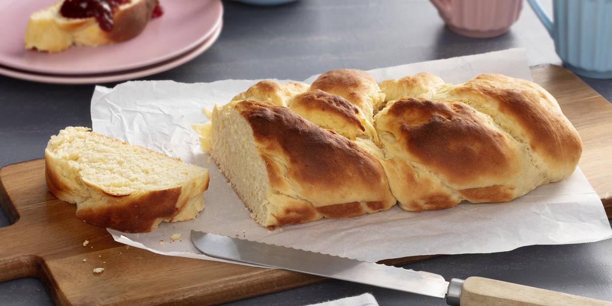 Fotografia em tons de amarelo e rosa de uma bancada, ao centro o pão de mandioquinha sobre um papel manteiga em uma tábua e ao fundo pratos e xícaras rosas e azuis.