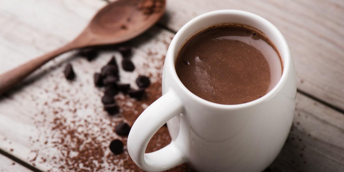 Fotografia em tons de branco e marrom tirada de uma bancada marrom, contém uma xicara branca com chocolate quente dentro e ao lado uma colher de madeira e chocolate em pó espalhado pela bancada.