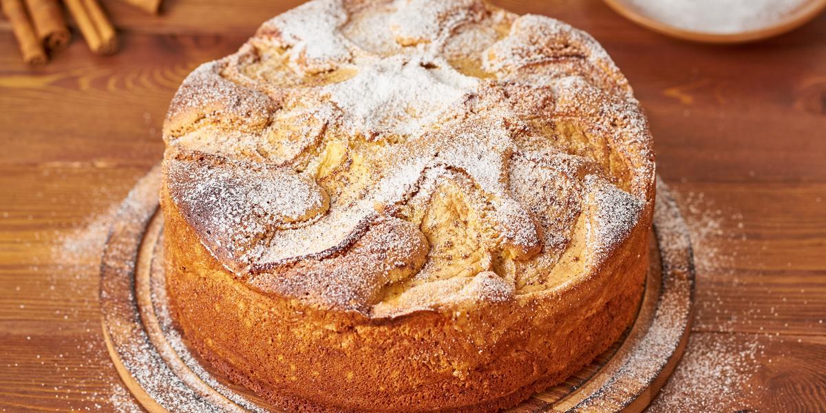 Fotografia em tons de marrom e pardo de uma bancada de madeira marrom vista de cima, ao centro um bolo redondo com açúcar por cima para decorar. Ao lado canelas e um prato redondo com açúcar