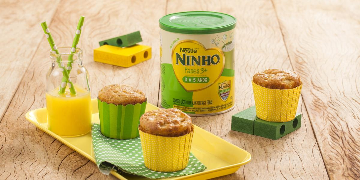 Fotografia em tons de amarelo e verde em uma bancada de madeira clara, um recipiente amarelo com dois cupcakes de maçã e aveia em forminhas amarela e verde. Ao lado, brinquedinhos infantis, uma lata de Ninho Fases e mais um cupacke.