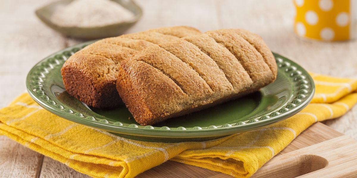 Fotografia em tons de amarelo em uma bancada de madeira clara, um pano amarelo com listras brancas, uma tábua de madeira, um prato verde redondo com dois pãezinhos em cima dele. Ao fundo, uma xícara amarela com bolinhas brancas.