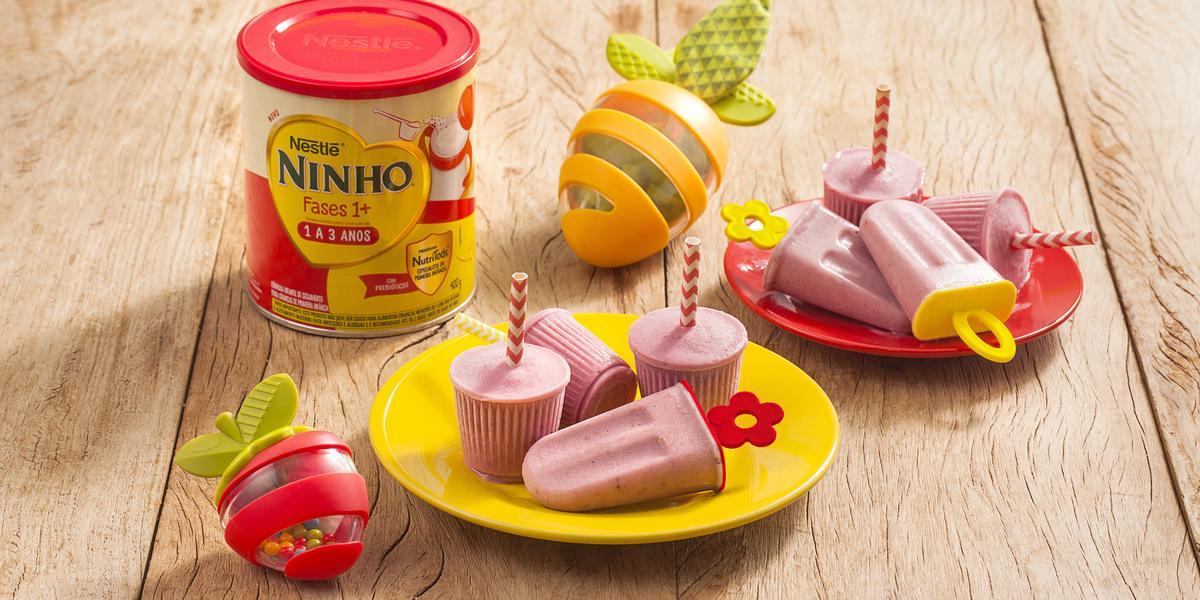Fotografia em tons de amarelo e vermelho em uma bancada de madeira clara, dois pratos vermelho e amarelo pequenos com picolés pequenos de banana e morango. Ao lado, um lata de Ninho Fases e brinquedinhos infantis.