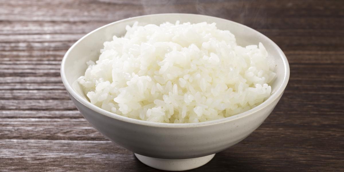 Fotografia em tons de marrom e branco de uma bancada de madeira vista de cima, um recipiente branco redondo contém arroz branco dentro.