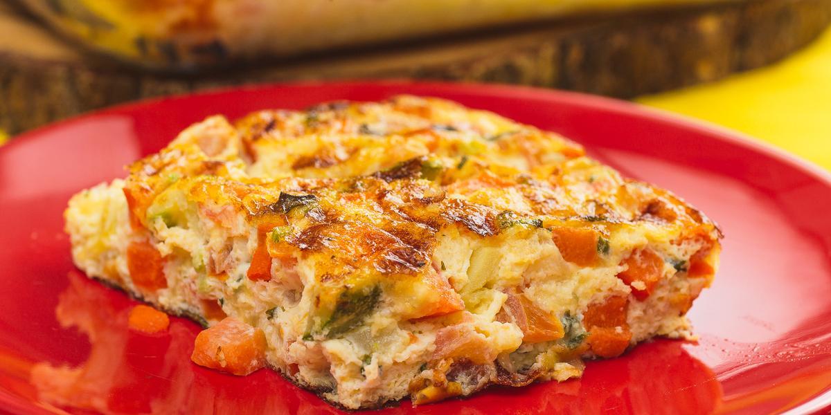 Foto bem aproximada de um prato redondo vermelho sobre o qual está uma fatia da receita de omelete de legumes.