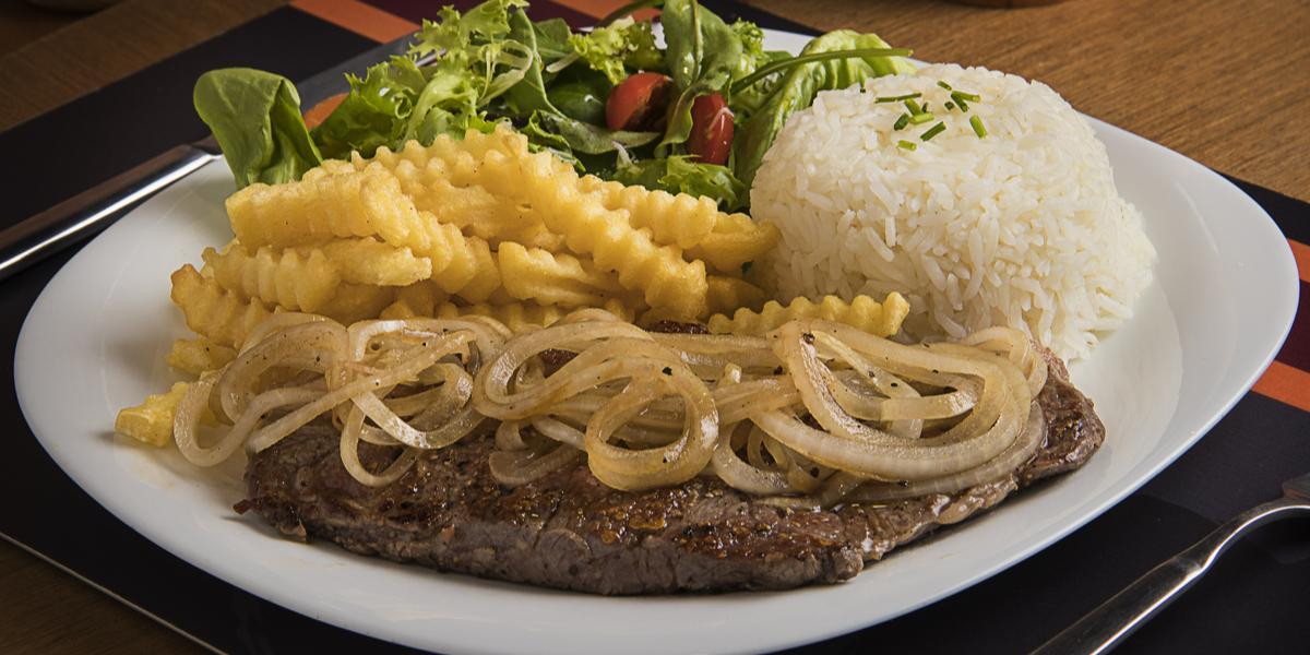 Fotografia em tons de marrom, branco e amarelo de uma bancada marrom, contém um prato redondo e branco com um bife com cebolas por cima, arroz, batatas fritas e salada como acompanhamento