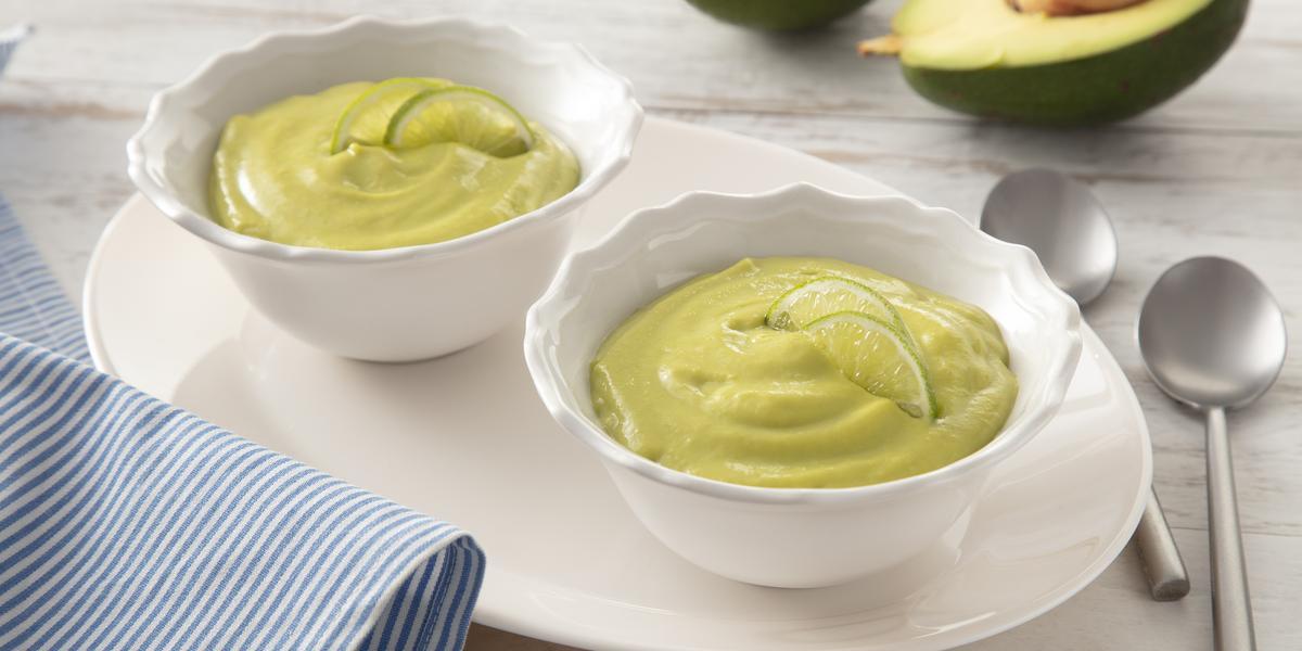 Fotografia em tons de branco e verde de uma bancada, ao centro dois potinhos com creme verde de abacate. Ao fundo, um abacate cortado ao meio.